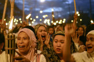 "ŒTAGUIG, PHILIPPINES - MARCH 06: Muslim women hold torches during a peace vigil in the Muslim community of Maharlika Village on March 6, 2013 in Taguig, Philippines. The peace rally was held to call for an end to hostilities in the ongoing crisis in Sabah. Fighting has broken out anew in the village of Lahad Datu, Sabah, Malaysia as Malaysian security forces comb the coastal areas where the ""Royal Sultanate Army of Sulu"" was thought to have been hiding. Around 200 armed followers of self-proclaimed Sultan of Sulu Jamalul Kiram III in the restive southern provinces of Sulu and Tawi-Tawi in Mindanao crossed over to neighboring Sabah last February 12 to lay claim to territory as ancestral land, triggering clashes with Malaysian security forces. Philippine diplomatic officials confirmed yesterday that security forces in Malaysia have conducted airstrikes and ground assault on the ""royal army"" of the Sultanate of Sulu in Lahad Datu, Sabah. A total of 17 followers of self-proclaimed Sultan of Sulu Jamalul Kiram III and eight Malaysian security forces were killed in the villages of Lahad Datu and Semporna in Sabah. (Photo by Dondi Tawatao/Getty Images)"