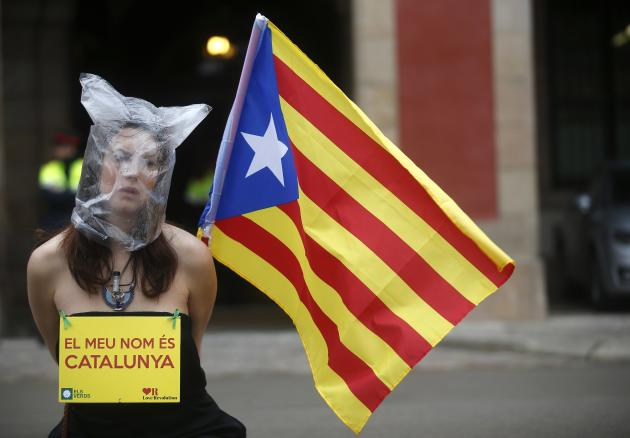 A pro-independence protestor sits in front of Catalonia's regional parliament as lawmakers voted inside, in Barcelona