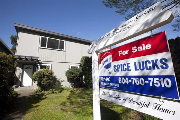 A for sale sign sits outside a home in Vancouver on April 8, 2010. Royal LePage says the price of a Canadian home is expected to rise by a relatively modest 2.9 per cent on average in 2015 as price appreciation slows across the country. THE CANADIAN PRESS/Jonathan Hayward
