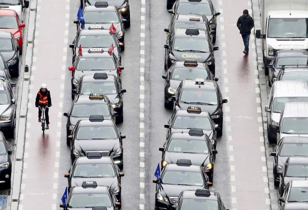 Taxi drivers line a street during a protest against online ride-sharing company Uber, in central Brussels