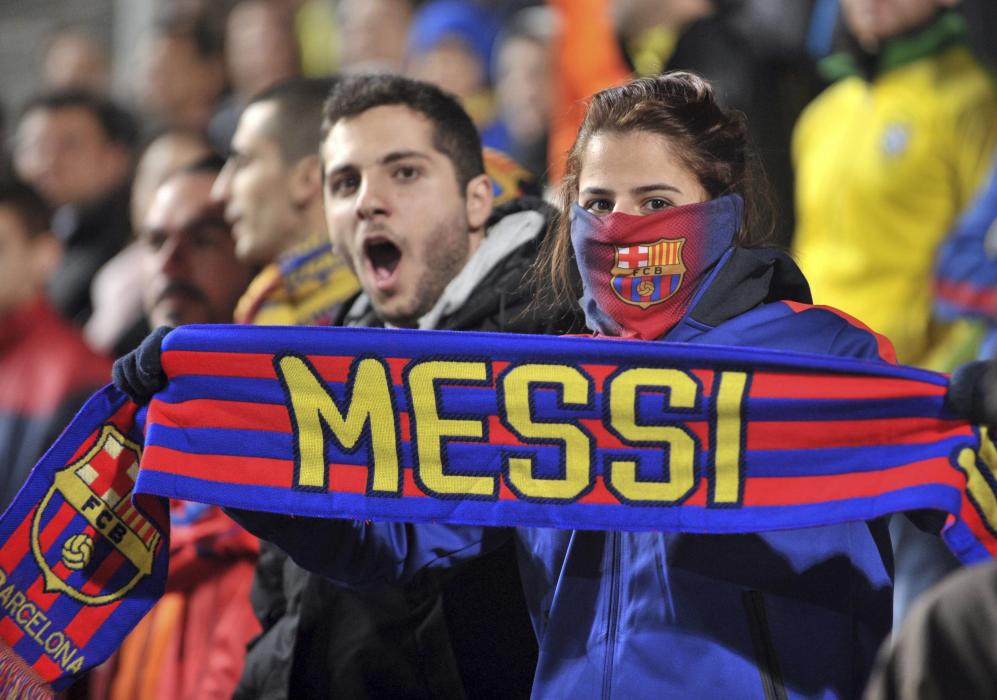 A Barcelona fan holds a scarf with Messi's name on it during the Champions League Group F soccer match between APOEL Nicosia and Barcelona in...