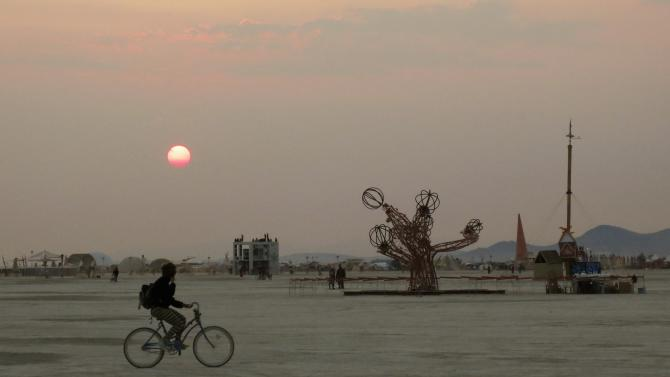 A participant bicycles past art works on the playa at sunrise, during the 2013 Burning Man arts and music festival in the Black Rock desert of Nevada
