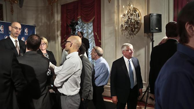NBA Deputy Commissioner Adam Silver, far left, speaks with reporters as NBA Commissioner David Stern, third from right, leaves after a press conference at the NBA board of governors meeting, Wednesday, Oct. 23, 2013 in New York. Stern will formally step aside on Feb. 1, 2014, after 30 years and Silver will become the new league commissioner
