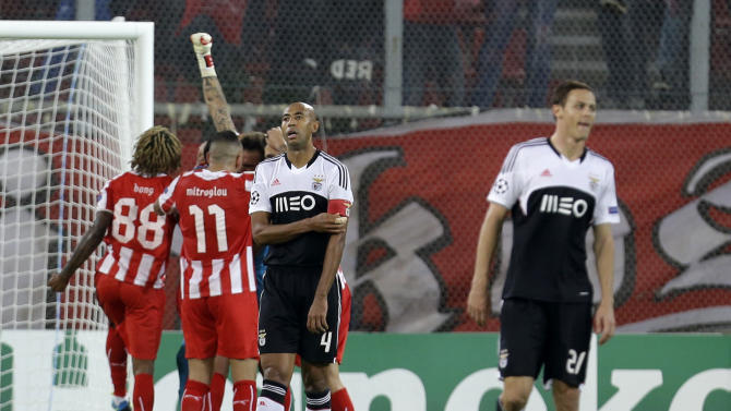 Olympiakos' players, background, celebrate their victory as Benfica's captain Luisao (4) and Nemanja Matic leave the pitch disappointed after their Champions League group C soccer match at the Karaiskaki stadium, in the port of Piraeus, near Athens, Tuesday, Nov. 5, 2013. Olympiakos won 1-0