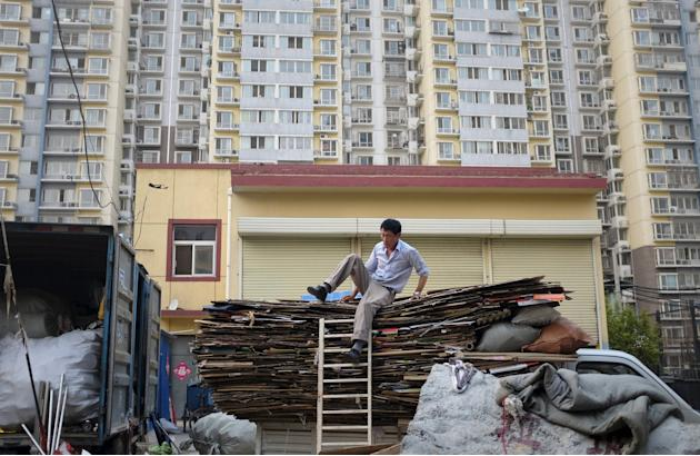 A rag-and-bone man tries to come down from a truck in front of an apartment block, in Beijing