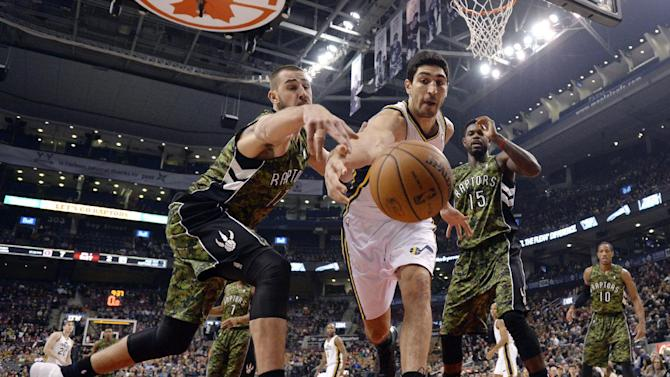 Utah Jazz center Enes Kanter, center, battles Toronto Raptors center Jonas Valanciunas, left, for the ball during the first half of an NBA basketball game in Toronto on Saturday, Nov. 9, 2013