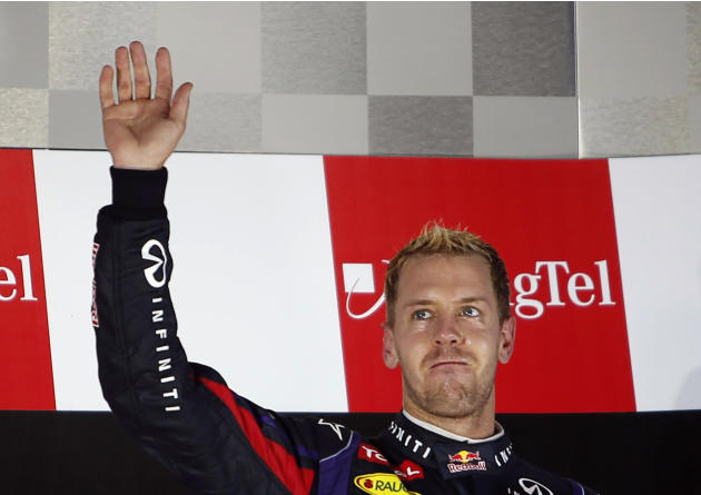 Red Bull Formula One driver Vettel waves on the podium after winning the Singapore F1 Grand Prix in Singapore