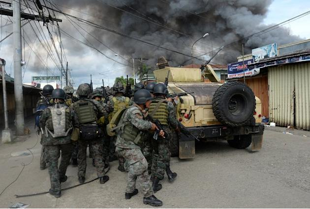 Philippines forces take cover during a fire fight with Muslim rebels in Zamboanga, Mindanao on September 12, 2013