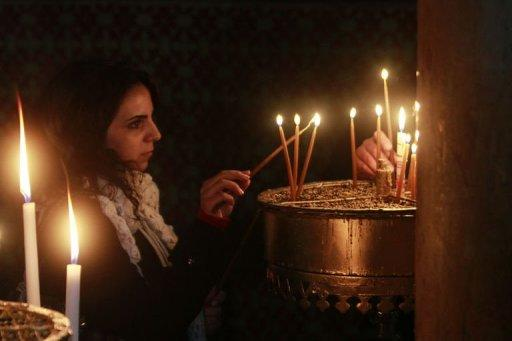A woman lights a candle at the Church of the Nativity, in the West Bank biblical town of Bethlehem, the traditional birthplace of Jesus as preparations for Christmas celebrations get underway on December 21, 2012.