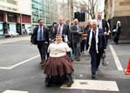 Lynette Rowe (C) with her legal team and supporters leaving the Supreme Court in Melbourne, July 18, 2012. Rowe aged 50 - born without arms and legs after her mother took thalidomide during pregnancy - won a landmark multi-million dollar settlement in her class action against drug firms