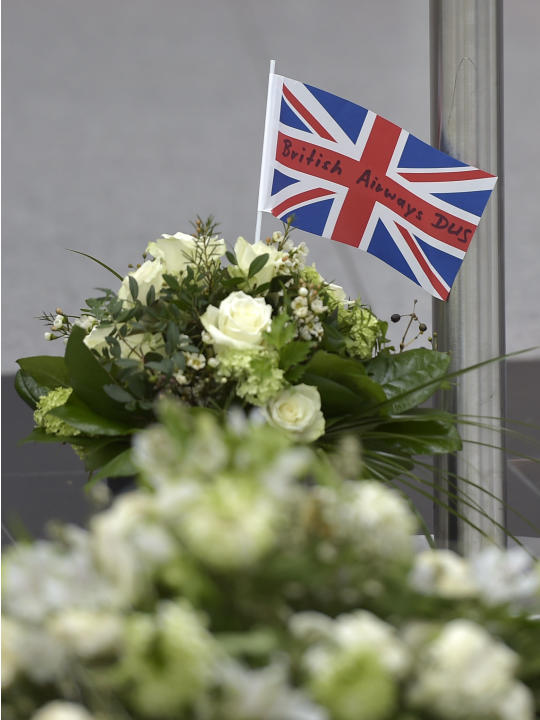 A flag from British Aiways sticks in a buquet of flowers for the victims of the plane crash at the airport in Dusseldorf , Germany, Tuesday, March 31, 2015. One week ago 150 people died in the Germanw