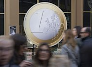 People walk in front of a restaurant displaying a giant Euro coin sticker in its window in Madrid, December 8, 2011. Japan has purchased 13 percent of the eurozone rescue fund's latest bond sale, a government official said Wednesday, as the region continues fundraising to help contain its sovereign debt crisis