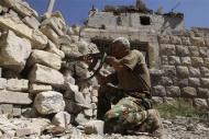 A Free Syrian Army fighter takes a position as he aims his weapon near Hanano Barracks, which is controlled by forces loyal to Syria's President Bashar al-Assad, in Aleppo September 11, 2013. REUTERS/Muzaffar Salman