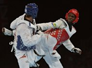 Turkey's Bahri Tanrikulu (blue) fights against Gabon's Anthony Obame during their men's taekwondo semi-final bout in the +80 kg category as part of the London 2012 Olympic games