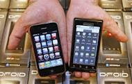 A manager holds an Apple iPhone (L) and Motorola's Droid smartphone (R) sold through Verizon at the Verizon store in 2009 in Orem, Utah. An American judge has dismissed lawsuits lodged by Apple and Motorola against each other for copyright infringement