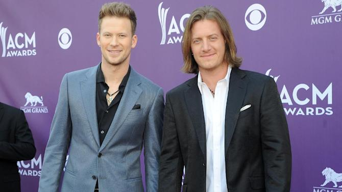 """FILE - This April 7, 2013 file photo shows Brian Kelley, left, and Tyler Hubbard, of the musical group Florida Georgia Line at the 48th Annual Academy of Country Music Awards at the MGM Grand Garden Arena in Las Vegas. Florida Georgia Line thought they were riding the whirlwind when their first single improbably made it to the top of the country charts late last year. Now that rapper Nelly has entered the picture and """"Cruise"""" is rocketing up the pop charts, Tyler Hubbard and Brian Kelley have discovered _ like Taylor Swift, Lady Antebellum and a few other country acts over the years _ there's nothing like the ride of a crossover hit. (Photo by Al Powers/Invision/AP, file)"""