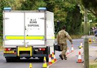 A British soldier from the bomb disposal squad prepares to enter the house of a family shot dead in the French Alps, in Claygate, in south-east England, on Spetember 10. Police sent a bomb disposal squad to the house after finding possible explosives in the latest dramatic twist in the case. Police also evacuated neighbouring homes