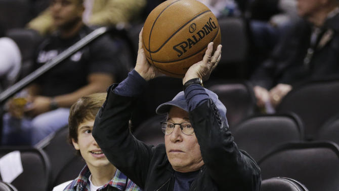 Musician Paul Simon returns a basketball as he attends an NBA basketball game between the San Antonio Spurs and the New York Knicks, Thursday, Jan. 2, 2014, in San Antonio