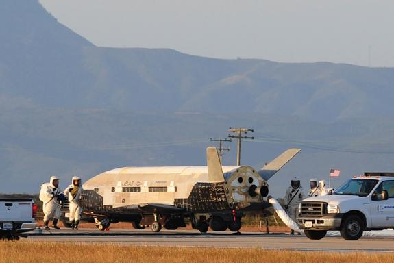 Technicians inspect the military X37-B space plane after its June 2012 landing.