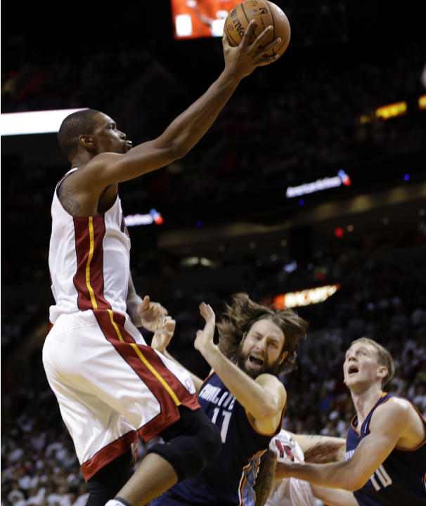 Miami Heat's Chris Bosh, left, shoots over Charlotte Bobcats' Josh McRoberts (11) during the first half in Game 2 of an opening-round NBA basketball playoff series, Wednesday, April 23, 2014,