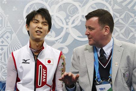 """Japan's Yuzuru Hanyu reacts with coach Brian Orser in the """"kiss and cry"""" area during the Figure Skating Men's Free Skating Program at the Sochi 2014 Winter Olympics, February 14, 2014. REUTERS/Lucy Nicholson"""