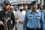 Pakistani policemen escort Islamic cleric Hafiz Mohammed Khalid Chishti (C) upon his arrival at a court in Islamabad on September 2, 2012. The cleric, who first gave police the burned papers as evidence of blasphemy against a young Christian girl, was detained in September for desecrating the Koran and tampering with evidence