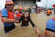 Rescuers help a woman cross a flooded street as residents are evacuated from their homes in the village of Tumana, Marikina town, in suburban Manila. Torrential monsoon rains flooded half of the Philippine capital on Tuesday, killing at least 16 people as rampaging waters swept away homes, destroyed bridges and triggered a landslide in a shanty town
