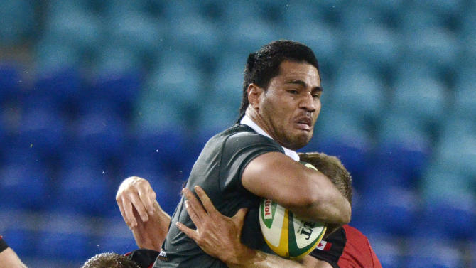 The Australian Barbarian's Sitaleki Timani makes a run with the ball against Canada during their rugby union match on the Gold Coast, Australia, Friday, Aug. 26, 2011. (AP Photo/Steve Holland)