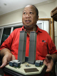 In this photo taken Aug. 4, 2011 at his home in Tagaytay City, south of Manila, Philippines, Rudy Abad, husband of Marie Rose Abad, holds a miniature replica of the World Trade Center twin towers he received as a memento during the first year anniversary of the terrorist attacks in New York City. Unlike many victims of the 2001 attacks who are remembered mostly by their family and friends, Marie Rose Abad's legacy lives on half-way around the world in a once-notorious Manila slum now turned into a tidy village that carries her name. (AP Photo/Pat Roque)
