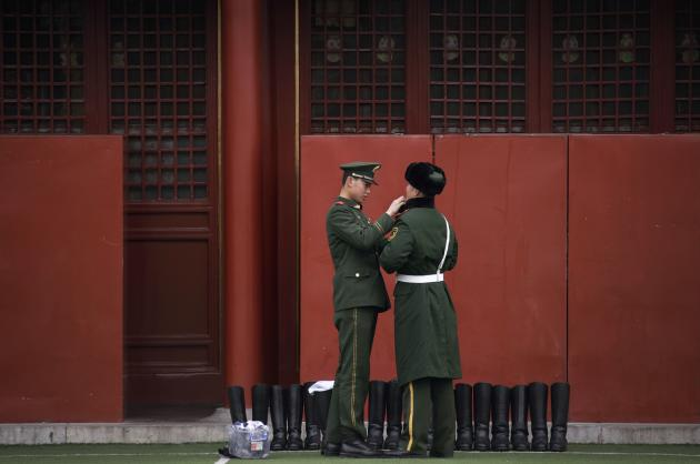A paramilitary police officer adjusts his colleague's uniform during the week-long Chinese New Year holiday at the Forbidden City compound in Beijing February 14, 2013. The Lunar New Year, or Spring Festival, began on February 10 and marks the start of the Year of the Snake, according to the Chinese zodiac. REUTERS/Petar Kujundzic (CHINA - Tags: MILITARY ANNIVERSARY SOCIETY)