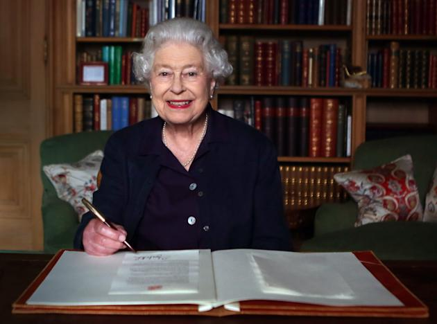 Embargoed to 0001 Wednesday October 9. Previously unreleased photo dated 27/09/2013 of Queen Elizabeth II sitting at a desk at Balmoral, Royal Deeside, as she signs a message that will travel in the Glasgow 2014 Baton as it is carried throughout the Commonwealth ahead of the Glasgow 2014 Commonwealth Games.