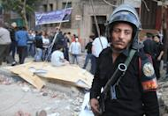 An Egyptian riot policemen stands guard at the spot where Coptic Christians came under attack by assailants throwing stones and bottles at them in Cairo in 2011. Despite gestures by Egypt's interim military leaders towards greater inclusiveness, sectarian violence has increased, a US report says