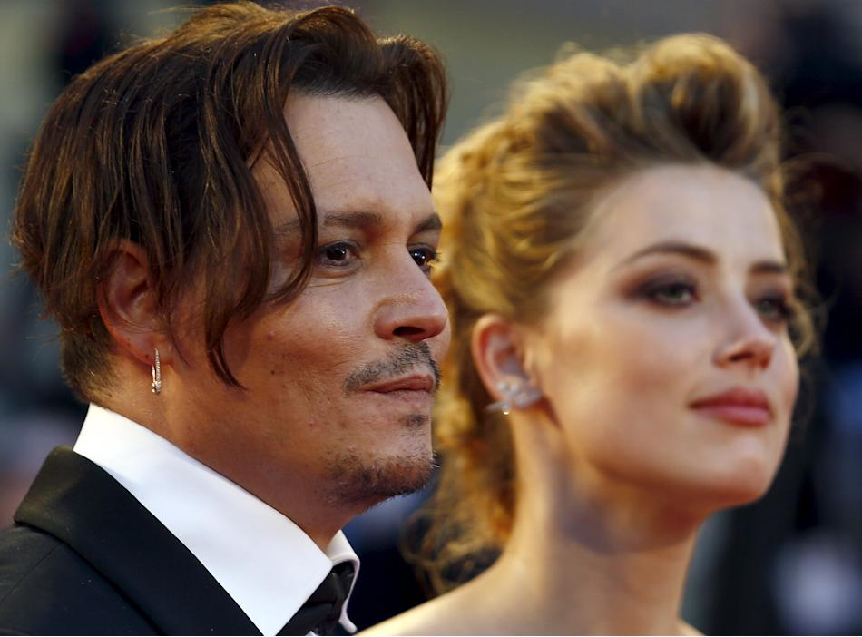 Actress Amber Heard and her husband Johnny Depp attend the red carpet event for the movie