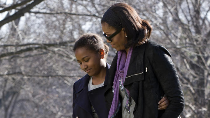 FILE - This Jan. 6, 2013 file photo shows first lady Michelle Obama, right, with her daughter Sasha on the South Lawn of the White House in Washington after returning from vacation in Hawaii. Michelle Obama has proven her fashion savvy time and time again since she was introduced to the country as first lady on Inauguration Day 2009. In the past four years she has adeptly walked the line between directional fashionista and everywoman. (AP Photo/Jacquelyn Martin, file)