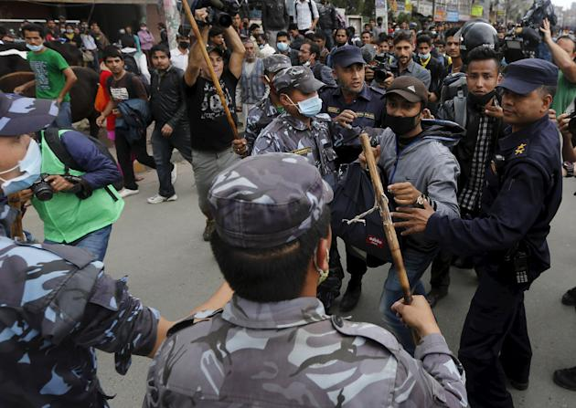 Earthquake victims scuffle with Nepalese police personnel as they try to block traffic along a road, while protesting against the government's lack of aid provided to the victims in Kathmandu