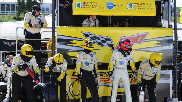 Corvette driver Oliver Gavin, second from right, of England, waits for a pit stop during the American Le Mans Series' Petit Le Mans auto race at Road Atlanta, Saturday, Oct. 1, 2011, in Braselton, Ga.  (AP Photo/Rainier Ehrhardt)