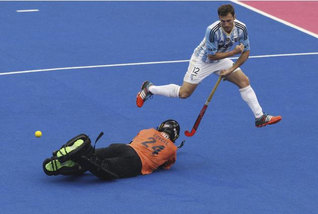 FILE - In this Dec. 11, 2014 file photo, Australia's goalkeeper Tyler Lovell, on ground, prevents a goal attempt by Argentina's Lucas Vila during the Champions Trophy field hockey quarter fina