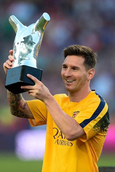 Barcelona's Argentinian forward Lionel Messi lifts up his UEFA Best Player in Europe Award before their Spanish league football match against Malaga CF at the Camp Nou stadium in Barcelona, August