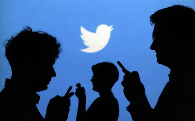 People holding mobile phones are silhouetted against a backdrop on which the Twitter logo is projected, in this file picture illustration taken in Warsaw on September 27, 2013. REUTERS/Kacper Pempel/Files