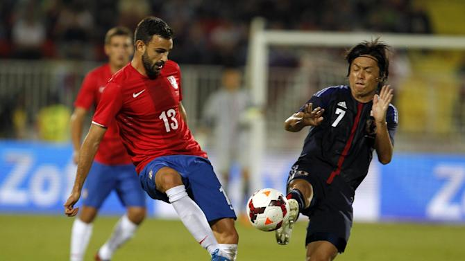 Serbia's Ivan Radovanovic, left, challenges for the ball with Japan's Yasuhito Endo during the farewell match of retiring Serbian  soccer player Dejan Stankovic, at Karadjordje stadium in Novi Sad, Serbia, Friday, Oct. 11, 2013. Stankovic has played for Red Star Belgrade (1994-1998), Lazio (1998-2004) and Inter Milan (2004-2013). After this match Stankovic will have the largest number of appearances in Serbian national team history