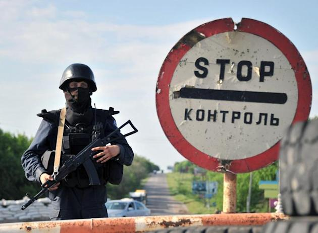 Ukrainian troops stand guard at a checkpoint on the road near the eastern city of Izum in Donetsk region on May 15, 2014