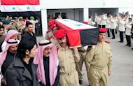 A photo released by the Syrian Arab news Agency (SANA) shows Syrian military police carrying the coffin of a member of either the army or security forces, who was killed following days of unrest, as they transport his body from the October Military hospital in Damascus for burial