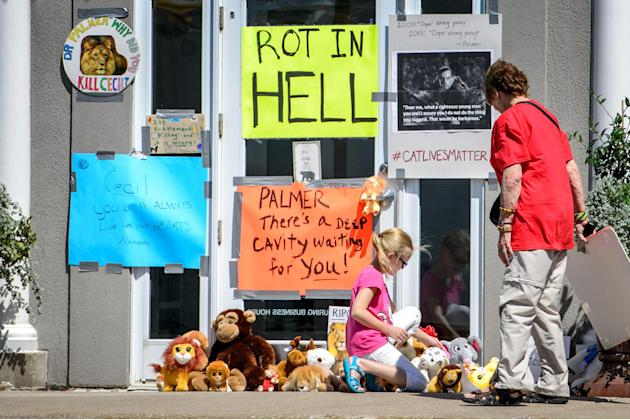 Protestors leave signs and stuffed animals in front of Dr. Walter Palmer's dental practice, Wednesday, July 29, 2015, in Bloomington, Minn. Palmer has been under fire since his involvement in the