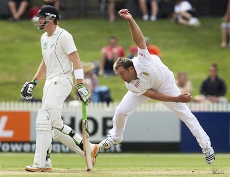 South Africa's Jacques Kallis (R) bowls past New Zealand's Martin Guptill on day one of their second international cricket test match in Hamilton March 15, 2012. REUTERS/Nigel Marple/Files