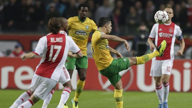 Celtic's Beram Kayal, center, clears the ball ahead of Ajax's Daley Blind, left, and Ajax's Siem De Jong, rear right, during the Champions League Group H soccer match between Ajax Amsterdam and Celtic Glasgow at ArenA stadium in Amsterdam, Netherlands, Wednesday, Nov. 6, 2013