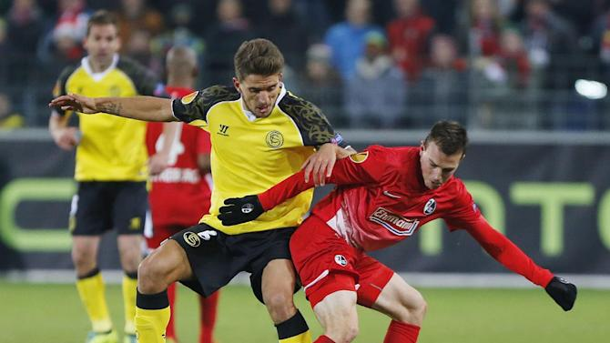 Freiburg's Vladimir Darida of Czech Republic, left, and Sevilla's Daniel Carrico challenge for the ball during a Group H Europa League match between SC Freiburg and Sevilla FC in Freiburg, Germany, Thursday, Dec.12, 2013