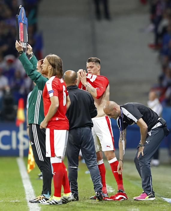 Switzerland's Granit Xhaka changes his shirt as Michael Lang waits to come on as a substitute