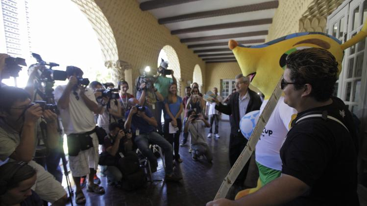 Brazilian soccer fan Anderson poses for the media after picking up his FIFA 2014 World Cup tickets in Rio de Janeiro