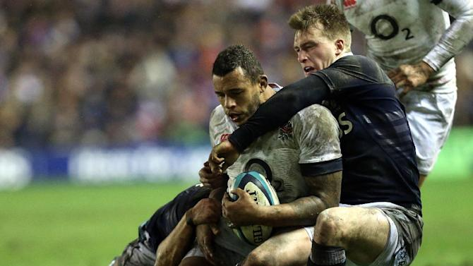 England's Courtney Lawes, left, is tackled by Scotland's Stuart Hogg, right, during their Six Nations rugby union international match at Murrayfield, Edinburgh, Scotland, Saturday Feb. 8, 2014