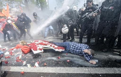A man lies on the ground as Turkish police use a water cannon to disperse protestors during a May Day rally near Taksim Square in Istanbul on May 1, 2015